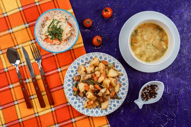 Вкусный обеденный набор из трех блюд: суп с лапшой и морковью, картофель с фасолью и морковь.