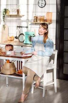 ノートにレシピを書く白人女性の肖像画。自宅の台所で。
