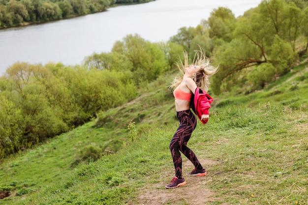 感情的なスポーツ女性が屋外の川の土手で踊っています。