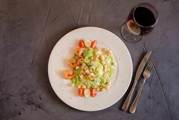Салат цезарь с креветками на белом фоне, бокал вина и вилка и нож на сером фоне текстурированных. меню ресторана. пример сервера.