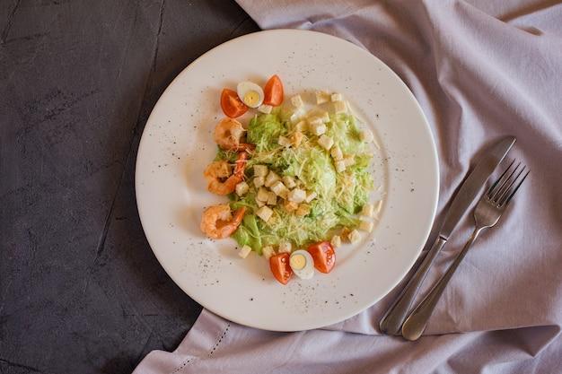 Салат цезарь с креветками на сером столе с полотенцем декора.
