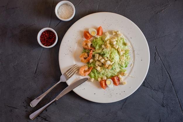 Салат цезарь с креветками, свежий и вкусный. белая тарелка с салатом на сером фоне.