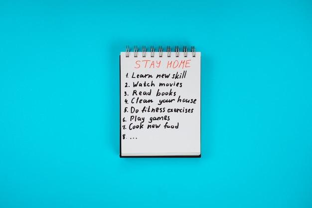 青色の背景に検疫アクティビティのチェックリストが付いた家のメモ帳に滞在します。家にいる-安全を保つ。