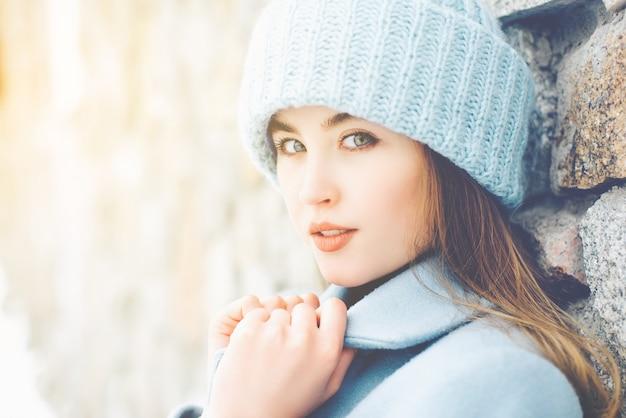 青いオーバーコートと帽子を着ている若い美しい女性の冬の肖像。カメラを見てください。