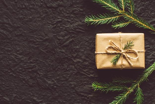 Подарочная коробка и еловые ветки на черном фоне