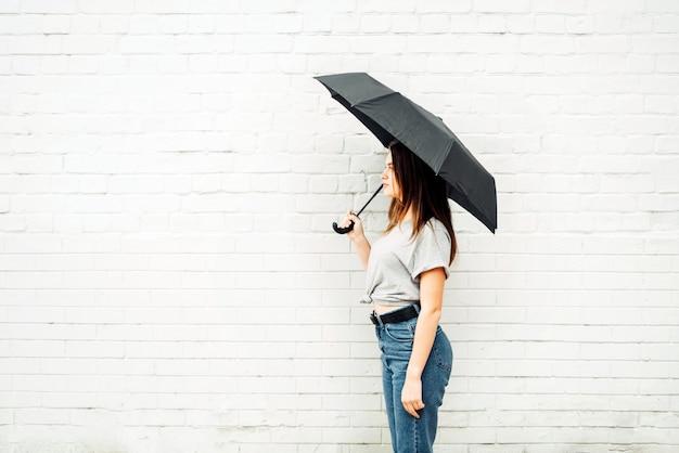 若い女の子は黒い傘で立っています。