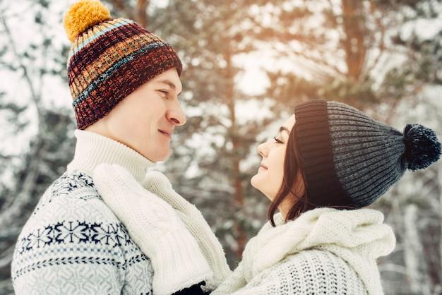 女の子と男はお互いを見ています。冬の屋外で愛するカップル