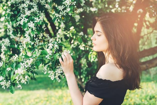 Весенний портрет молодой брюнетки с цветущей яблоней
