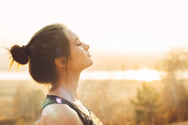 太陽の下でかなり若い女性のクローズアップの肖像画。朝のジョギングやアウトドアスポーツ