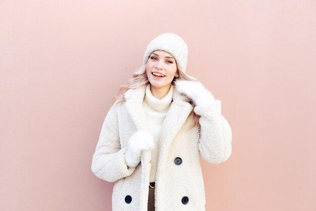 Портрет довольно блондинка в зимней одежде на фоне розовой стены на улице
