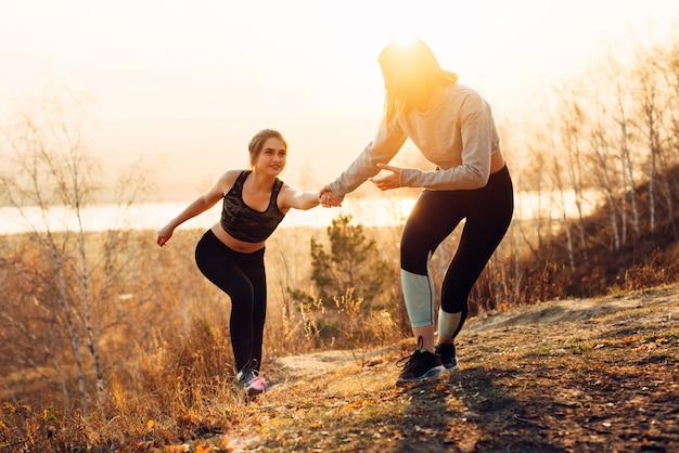 自然の中でジョギングする若い女性。ガールフレンドは、彼女の友人が斜面を登るのを手伝います。