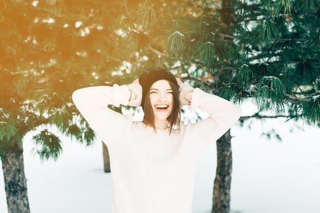 セーターの若い女性は最初の雪を喜んで、笑います