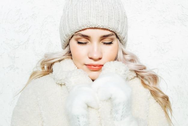 Красивый зимний портрет молодой женщины с глазами закрыт на белом фоне стены.