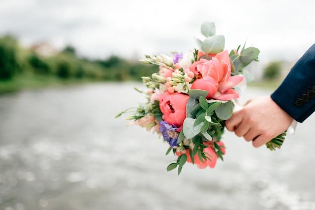 川で結婚式のブーケを持っている男性の手