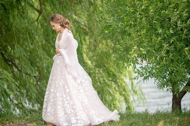 花の花束と屋外ポーズ白いウェディングドレスの美しい若い花嫁