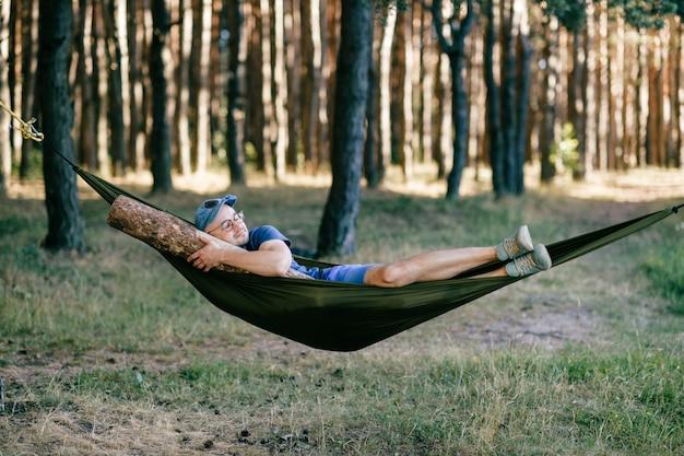奇妙な奇妙な奇妙な珍しい男性人。木の中で自然に巨大な木製のログとハンモックで寝ている異様な面白い狂気愚かな男。ベッドにビームあり。