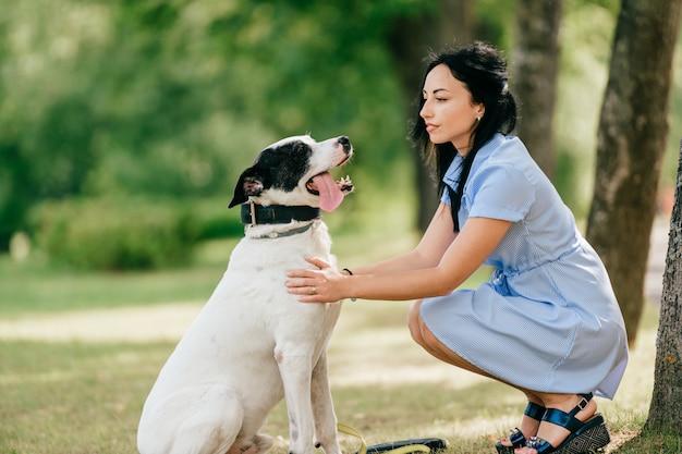 Молодая красивая брюнетка веселая девушка в голубом платье повеселиться и играть со своей мужской белой собакой, открытый на природе. симпатичная женщина любит доброго питомца.
