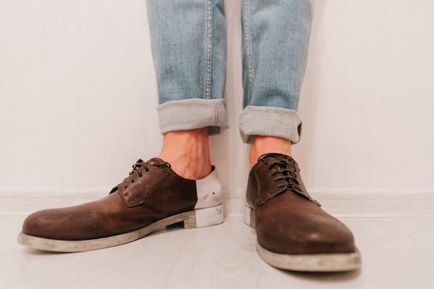 ジーンズと白い背景の上の茶色の革の靴で男性の足。