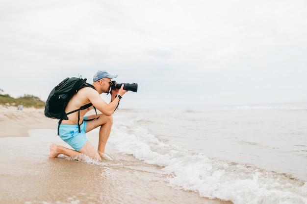 Человек с фотоаппаратом фотографировать море. человек фотограф размещения на пляже и принимая фото природы