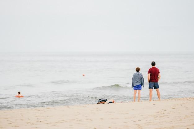 Взгляд от задней части мужчины и женщины смотря на море