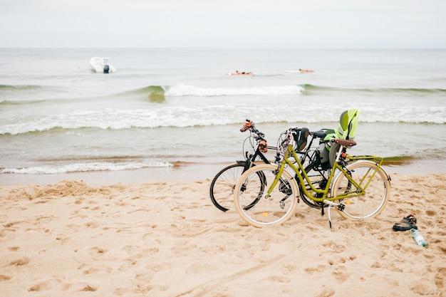 Два велосипеда стоят на пляже против моря.