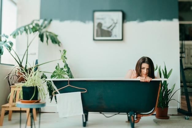 緑の植物とフランス風の部屋の装飾的な内部空のヴィンテージ鋳鉄風呂に横たわっているピンクのドレスで美しい少女の奇妙な肖像画。