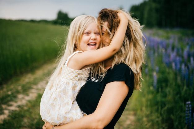 夏の畑で手で笑って幸せな娘を穴かがり面白い母。