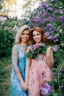 Очаровательны счастливые веселые сказочные сестры-близнецы в разных красивых летних платьях, позирует в весеннем цветущем парке.