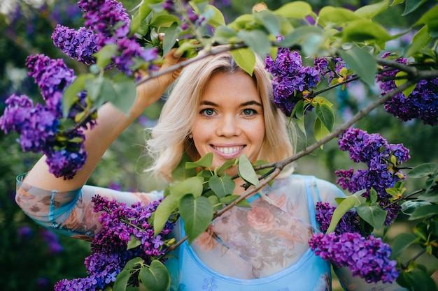 Портрет молодой красивой счастливой жизнерадостной усмехаясь положительной белокурой девушки смотря через ветви с белыми и фиолетовыми цветками в парке лета зацветая.