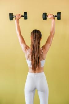 Атлетик женщина культурист с гантелями. красивая брюнетка с мышцами, поднятие тяжестей