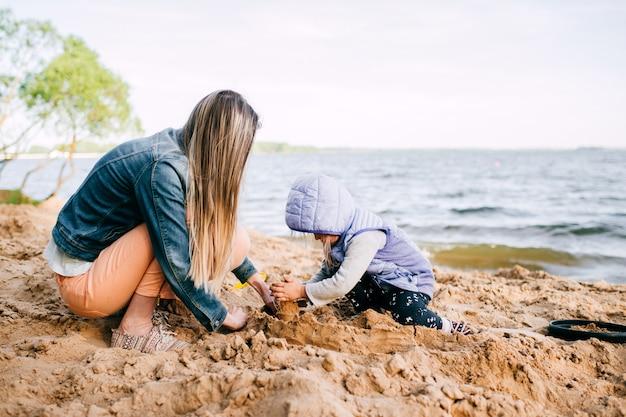 Молодая женщина с ее ребенком, строительство замка в песке на пляже возле моря. родитель с забавным детским образом жизни портрет. материнство и детство. счастливая семья на открытом воздухе.