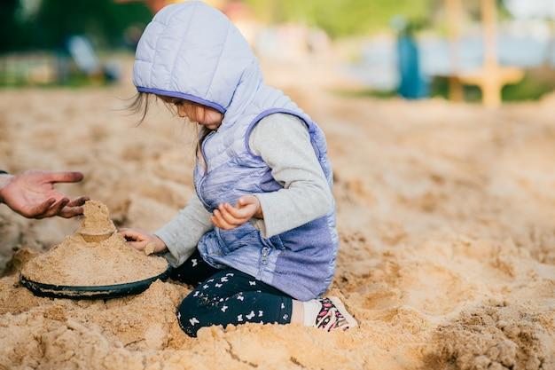 思いやりと子供のための遊び場のビーチで素敵な娘と遊ぶ父。海の向こうの自然で夏に一緒に幸せなライフスタイル家族