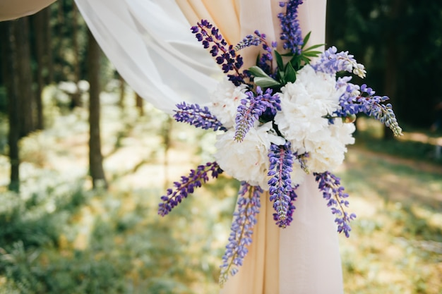 Свадебная деревянная арка для свадебной церемонии украшена голубыми полевыми цветами.