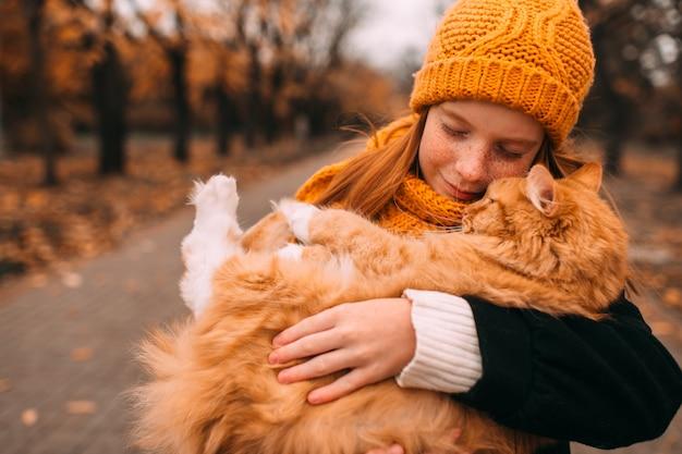 Очаровательная веснушка с добрым выражением лица держит рыжего кота в долине осеннего парка