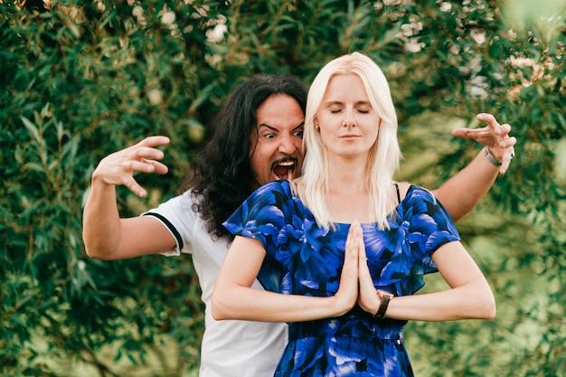 Смешная пара на открытом воздухе. странные люди. кричащий итальянский мужчина атакует молящуюся женщину сзади