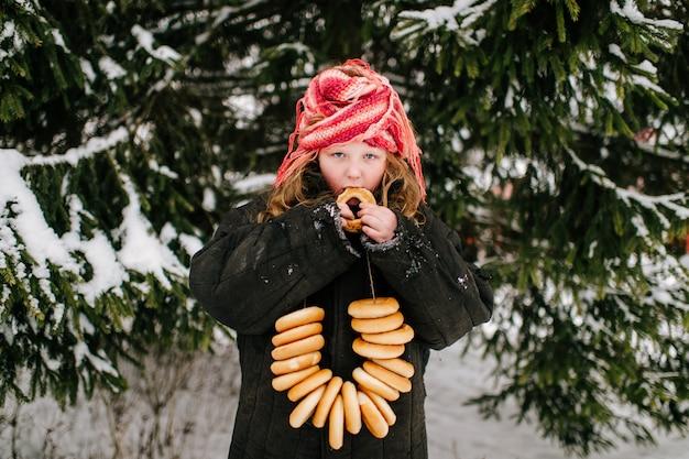 冬の日に雪の上のベーグルを食べる大人の特大の服で面白い女の子。ロシアの国の伝統的な休日を祝う