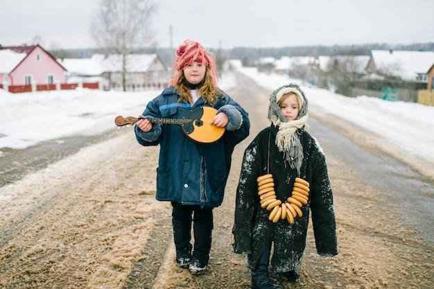 屋外の面白い子供たち。村の若者。ロシア風の伝統的な服。二人の少女が奇妙な珍しい奇妙な肖像画。大人用の特大の服を着ている子供。