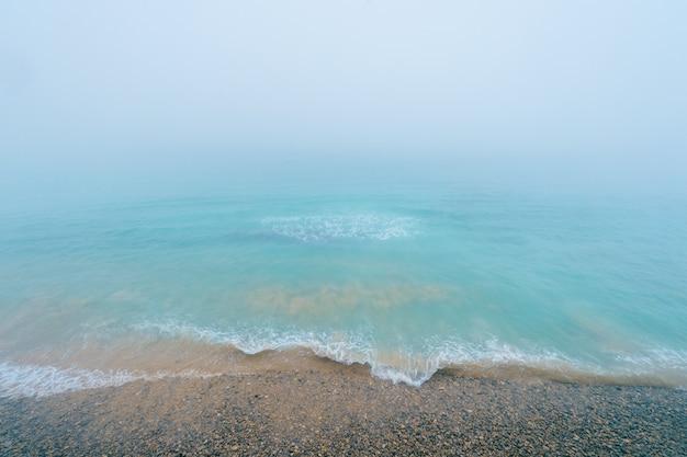 Удивительный тропический рай. вид сверху на океан с плавающими волнами. берег острова сокровищ. туманный и туманный морской пейзаж.