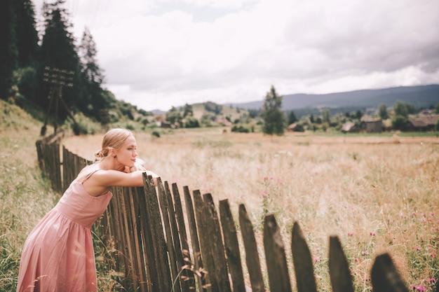 木製のフェンスの上に横たわる彼女の手で自然にリラックスしたかわいい白人の女の子。