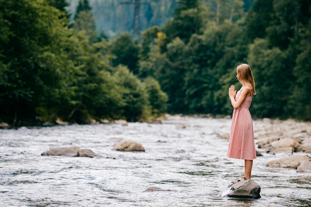Молодая девушка молится, стоя на камне в реке летом