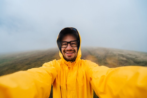 Улыбающийся человек путешественник в желтом плаще принимая селфи в туманный день на поле