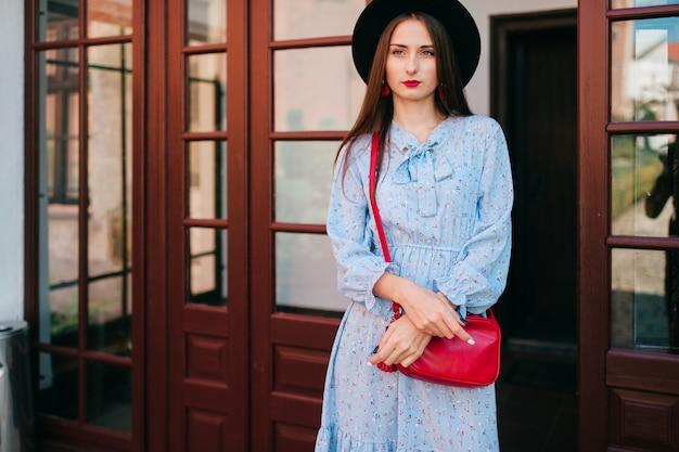 Элегантная молодая кавказская модель в голубом платье представляя перед дверью.