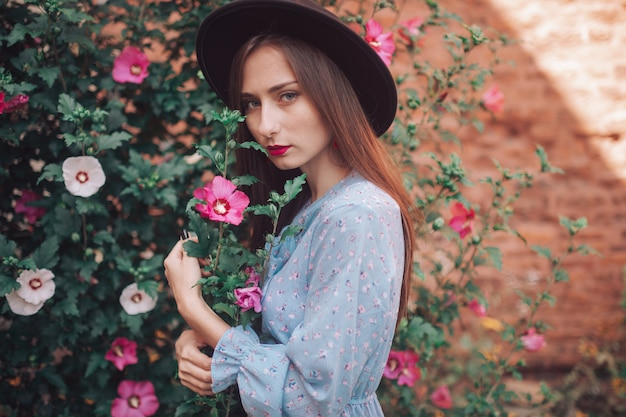 青いドレスと花が咲く庭でポーズをとってエレガントな帽子で官能的な女の子