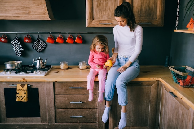 キッチンで彼女の小さな面白い娘と遊ぶ愛らしい若いお母さん。ハグ、運ぶ、彼女の小さな女性の子供を見ているかなりの母の肖像画。幸せな家族の屋内ライフスタイルの肖像画。