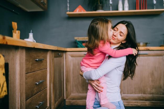 愛らしい若い母親が台所で彼女の小さな面白い娘を抱擁します。幸せな家族の屋内ライフスタイルの肖像画。