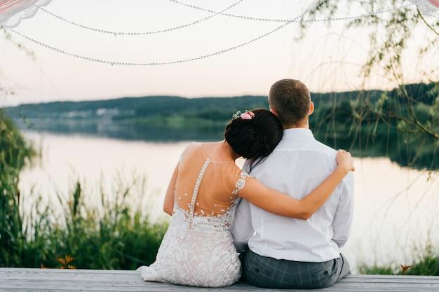 Романтический портрет сзади свадебных пар, сидя на деревянном пирсе на закате и наслаждаясь закатом над озером.