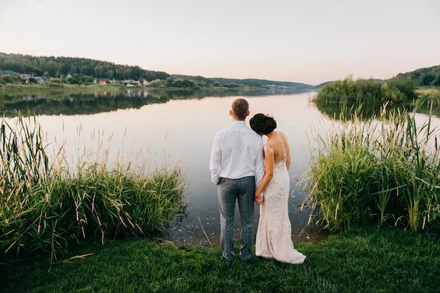 夕暮れ時の海岸に一緒に立って、湖の景色を楽しみながら結婚式のカップルの後ろからロマンチックな肖像画。