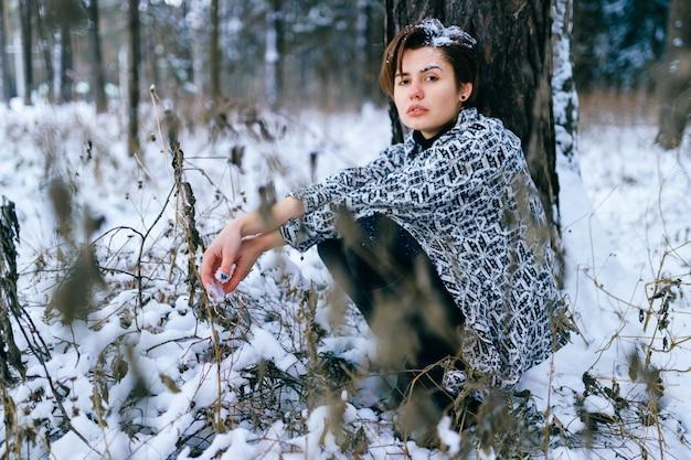 冬の雪に覆われた森に座っている孤独な少女のライフスタイルの肖像画。雪で覆われた悲しい感情的な貧しい顔と髪を持つ友好的な女性人