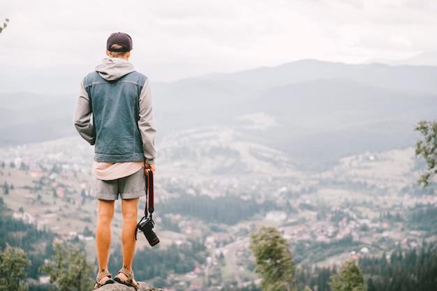 美しい風景と山の頂上に立っているカメラを持つ男