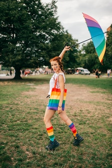 Девушка с рыжими волосами и флагом лгбт на лице, разноцветные несоответствующие носки